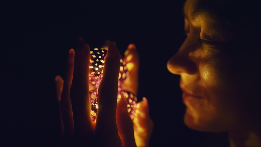 Magic hot light from lanterns falls on the woman eyes. The naked adult sexy caucasian girl lies at night on the bed and holds warm lamps in her hands. Christmas toy in black background. Indoor. | Shutterstock HD Video #1038220793
