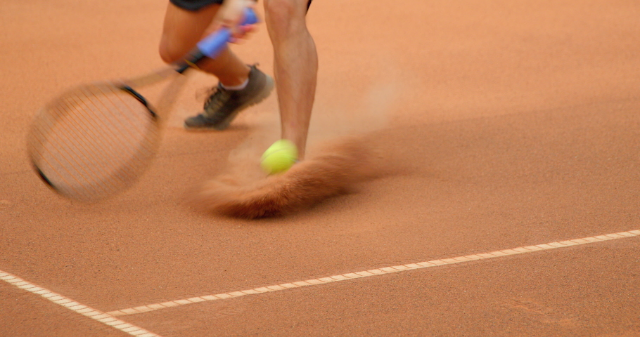 A tennis player slides across a clay tennis court in slow motion and plays the shot.