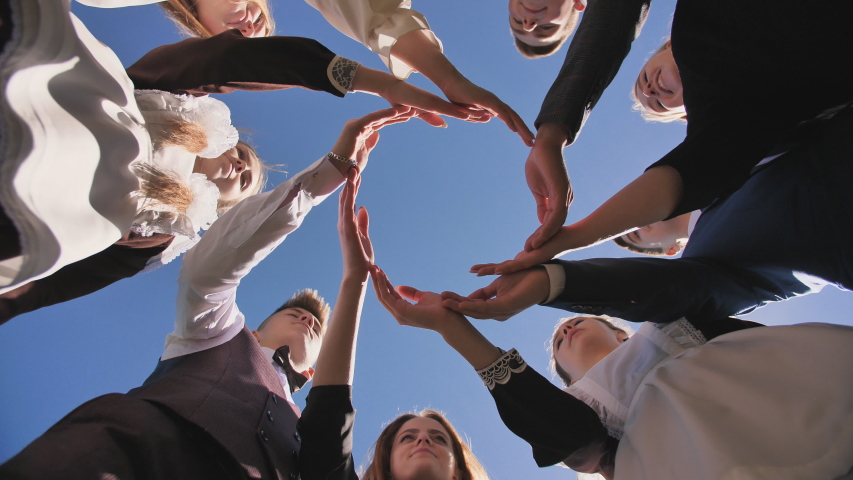 A group of graduate students make a circle from the palms of their hands.   Shutterstock HD Video #1038243683