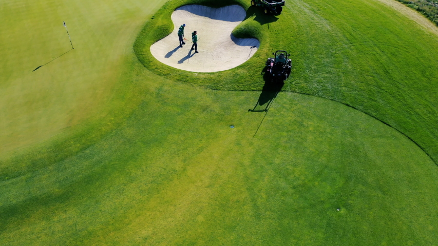 Staff on the golf course prepareing grass, bunkers and holes for the upcoming play.  Royalty-Free Stock Footage #1038244985