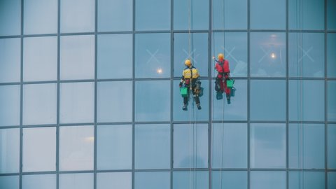 Two men workers in red and yellow work clothes cleaning the exterior blue windows of a skyscraper - industrial alpinism