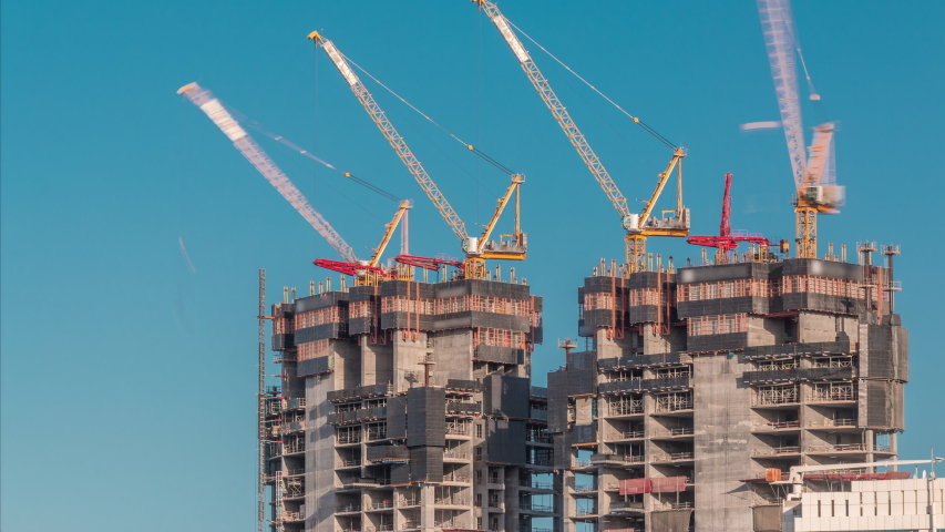 Aerial view of a skyscrapers under construction with huge cranes timelapse in Dubai marina. Blue sky on a background. United Arab Emirates