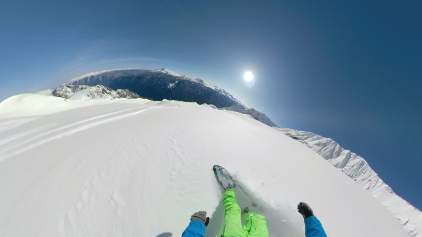 POV, OVERCAPTURE: Snowboarding off piste and shredding fresh powder on a perfect winter day in British Columbia. Snowboarders shredding the freshly fallen snow covering the picturesque Rocky Mountains