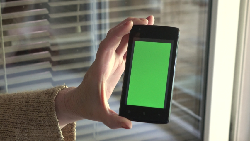 Smartphone with a green background on the screen. | Shutterstock HD Video #1038281327