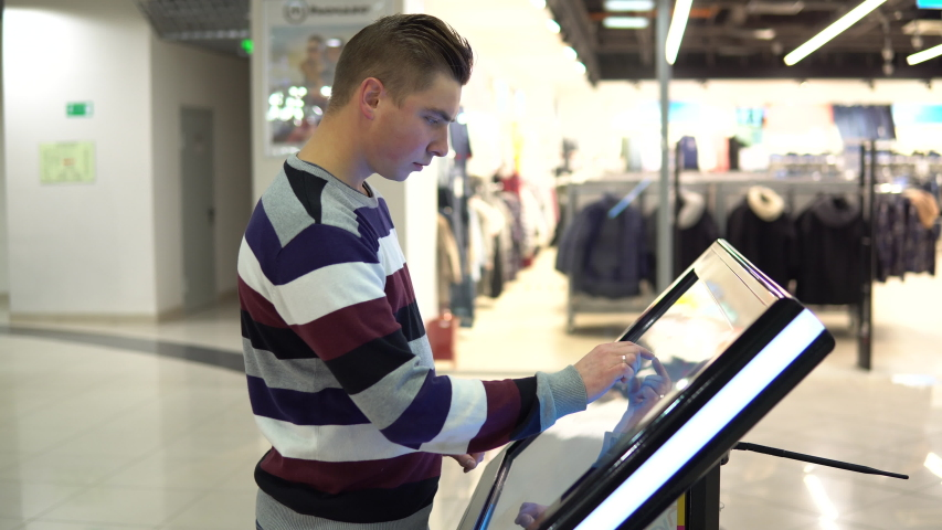 A young man is watching a navigation map on an electronic touch table in a shopping center. Royalty-Free Stock Footage #1038299759