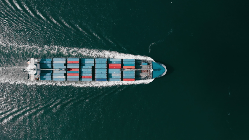 Aerial shot illustrating the process of ship transportation in Port Miami, USA. Cargo ship moves evenly on the water surface. Many containers loaded on the deck.