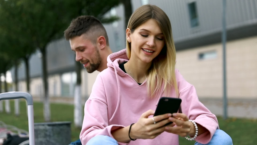 Traveling. Couple Using Phone, Waiting Transport Near Airport    Shutterstock HD Video #1038321548