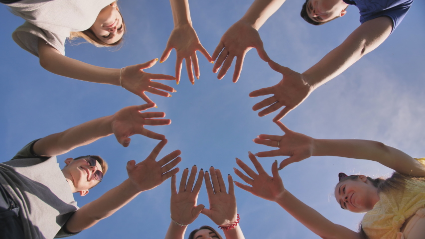 Friends make a circle shape from the palms of their hands.   Shutterstock HD Video #1038331481