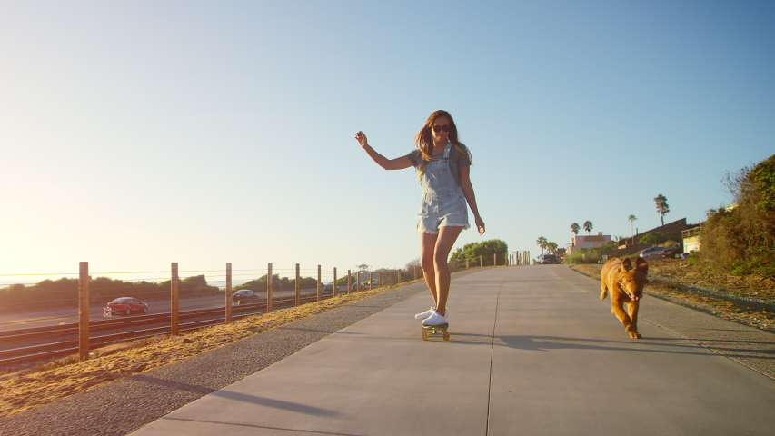 Young happy smiling girl skateboarding with golden retriever puppy at sunset | Shutterstock HD Video #1038333017
