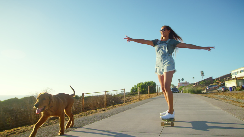 Young happy girl skateboarding with dog at sunset | Shutterstock HD Video #1038333032