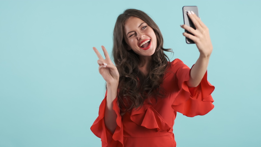 Pretty charming brunette girl in red dress joyfully showing peace gesture taking selfie on cellphone over blue background | Shutterstock HD Video #1038334634