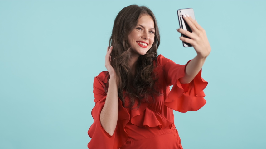 Attractive romantic brunette girl in red dress joyfully sending air kiss taking selfie on cellphone over colorful background | Shutterstock HD Video #1038334643