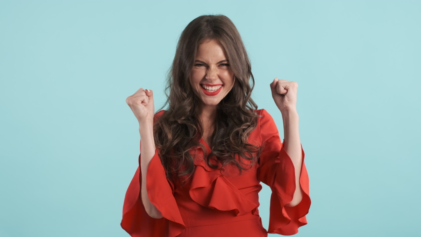 Beautiful charming brunette girl in red dress happily showing yes gesture and rejoicing on camera over blue background | Shutterstock HD Video #1038334649