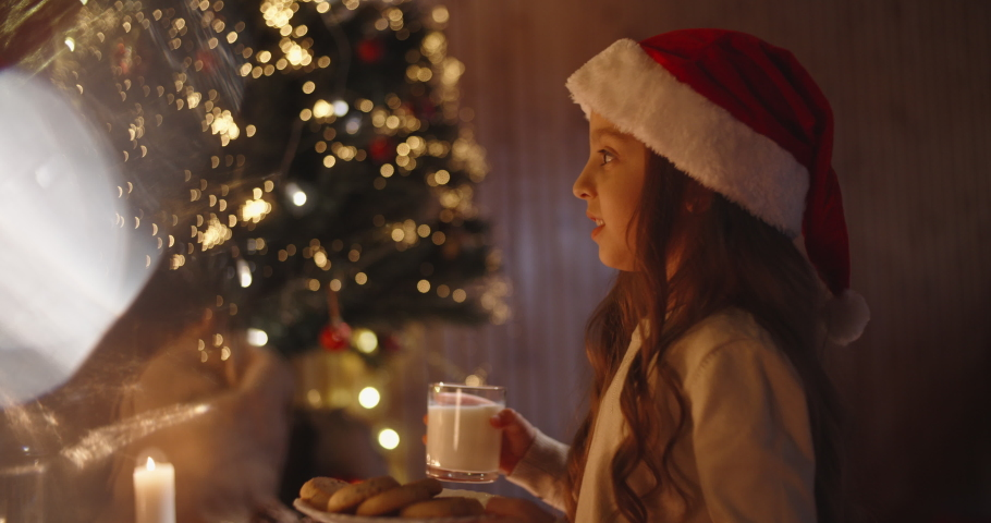 Little caucasian girl wearing christmas hat leaving cookies and milk near chimney for santa - holidays and celebrations, christmas spirit concept close up 4k