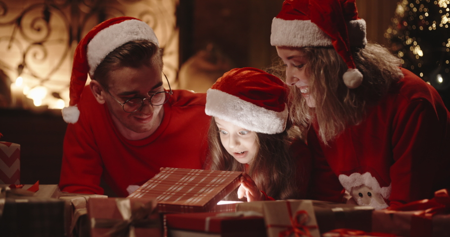 Caucasian family of three sitting in decorated room near christmas tree, little girl opening her christmas gift with something special - christmas spirit, togetherness concept 4k footage