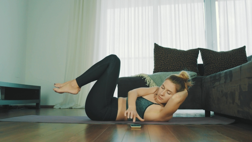 Young woman doing sports at home, Female fitness training in sportswear in the room    Shutterstock HD Video #1038346352