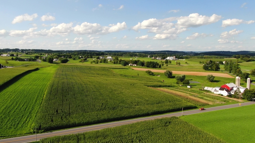 Aerial view of red barn and farmland in Lancaster County, Pennsylvania on sunny summer day with puffy clouds