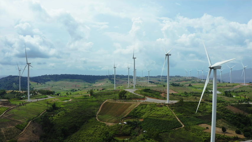 Aerial view of windmills farm for energy production on beautiful cloudy sky at highland. Wind power turbines generating clean renewable energy for sustainable development Royalty-Free Stock Footage #1038364820