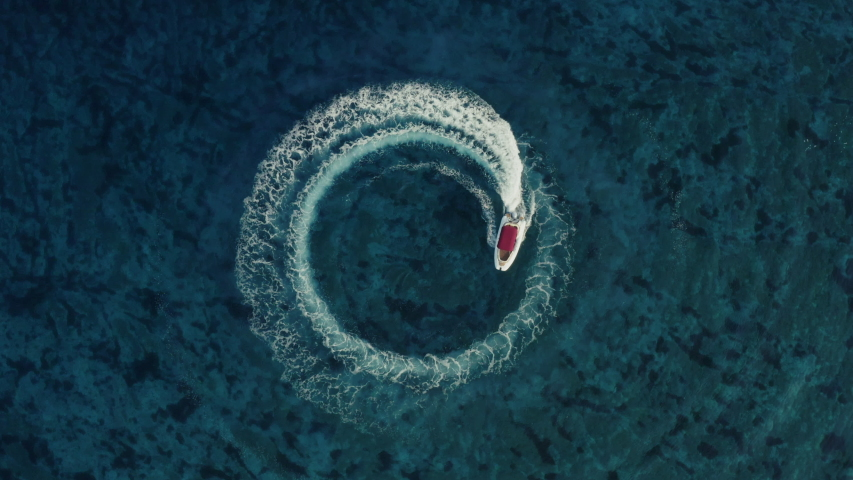 Slowmotion aerial shot of a fast speedboat with a red roof top driving around in the circle and making beautiful doughnuts in the clear turquoise magical sea. Top travel destination. 4K.