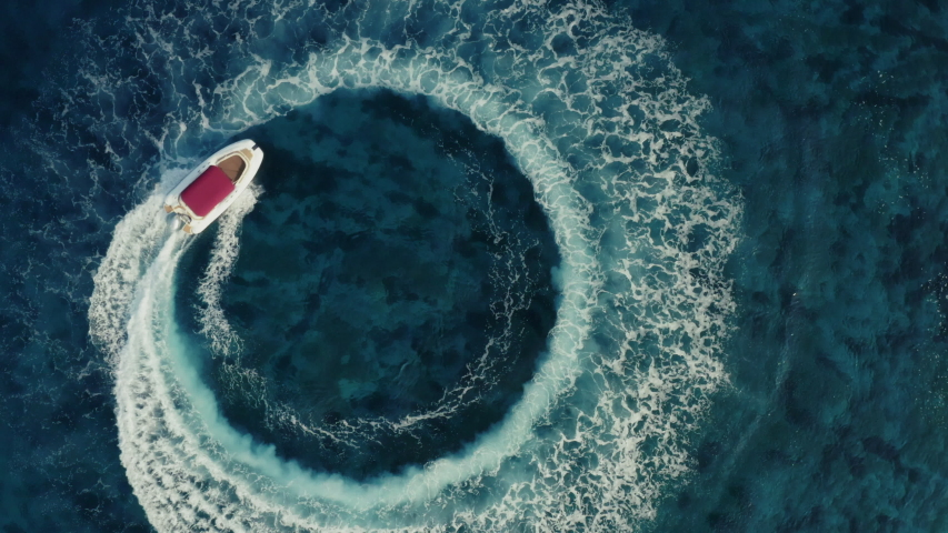 Slow motion aerial shot descending towards fast speedboat with a red roof top, going around in the circle and making beautiful shapes in the clear sea. Top travel destination. 4K. | Shutterstock HD Video #1038368363