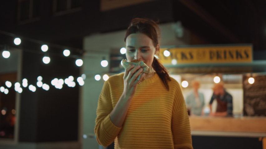 Beautiful Young Female Walks Away from a Food Truck with a Delicious Fresh Beef Burger. She's Happy with Hew Food and Takes a Biet. Commercial Kiosk is Selling Street Food on a Modern Cool Street.