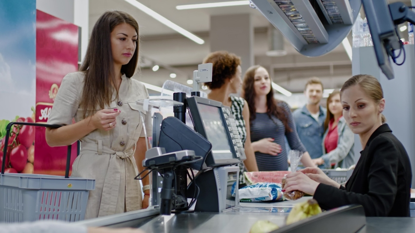 Woman paying with a smart watches in a grocery store