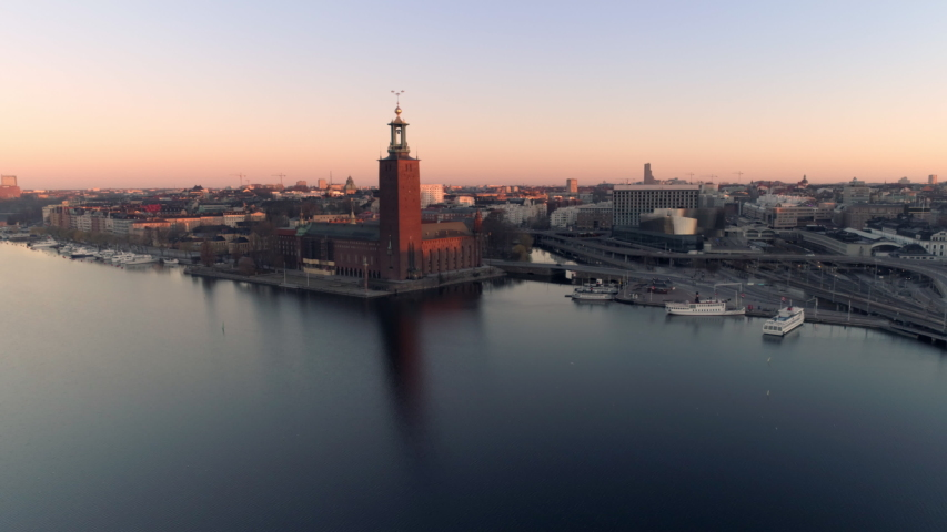 Aerial view of Stockholm City Hall and cityscape at sunrise. Drone shot flying over Riddarfjärden water, small harbor and bridges in the background. Town Hall, Stadshuset Skyline, Capital of Sweden Royalty-Free Stock Footage #1038378929