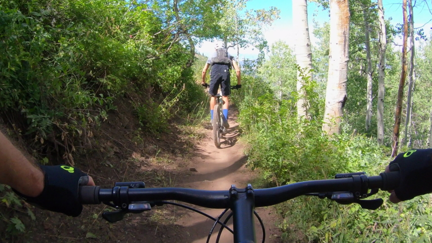 Point-of-view, P.O.V of mountain bikers on the Mid-Mountain single-track mountain bike trail in canyons village, Park City, Utah, Wasatch Mountains.  Go Pro footage shot in UHD.