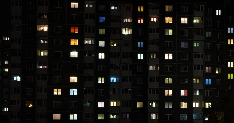 Night panorama time lapse of light in windows of multistory buildings with zoom. life in big city. Serenade of light