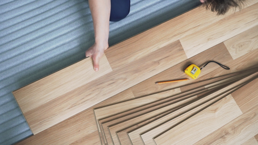 Man installing laminated floor, fitting tiles over white base layer, view from above   Shutterstock HD Video #1038405482