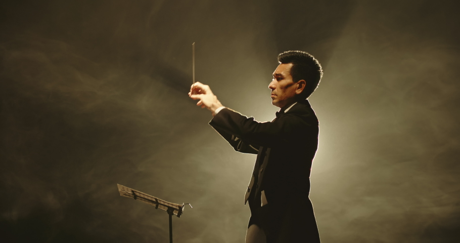 Male orchestra conductor controlling music in orchestra pit by movement of his hands and white baton, studio shot on black background 4k footage
