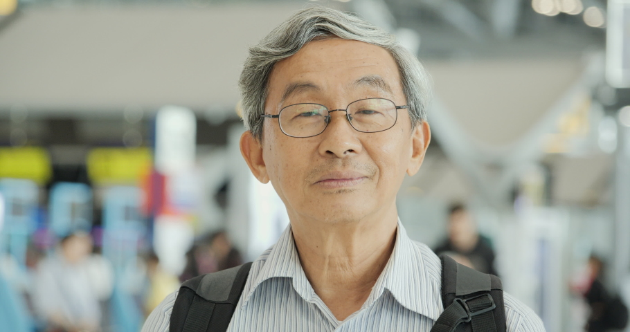 Portrait of senior man smiling at the flight timetable background in airport. | Shutterstock HD Video #1038413192
