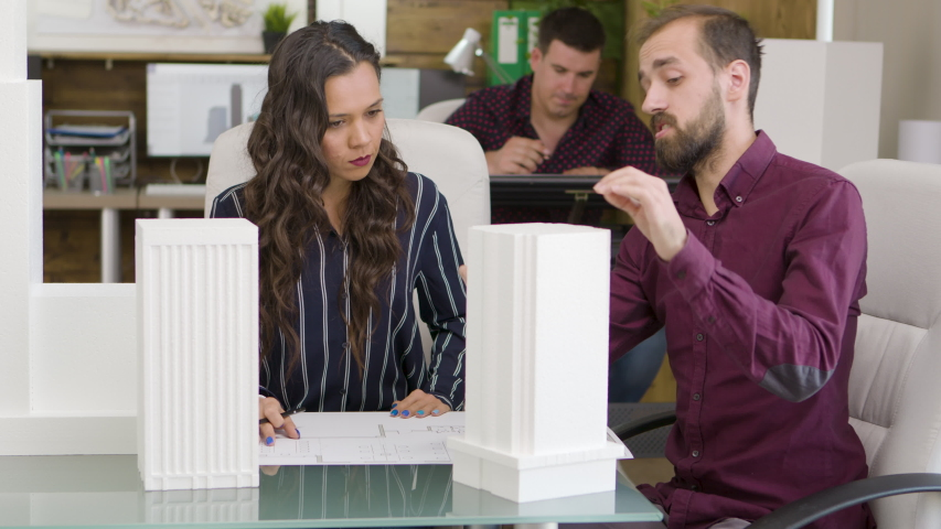 Female architect in a meeting with construction engineer about office buildings. Building models.  Modern corporate office business style, team communication, design professional work as team. Buildin | Shutterstock HD Video #1038418217