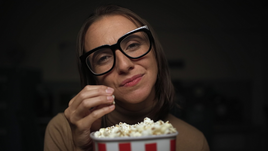 Happy woman eating popcorn and watching romantic movies at home