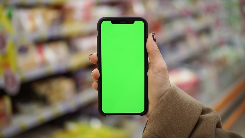 NEW YORK - April 22, 2019: Close up young hands woman hold use smartphone with vertical green screen in supermarket blurred background shopping fruit business food girl house shop healthy internet | Shutterstock HD Video #1038421559
