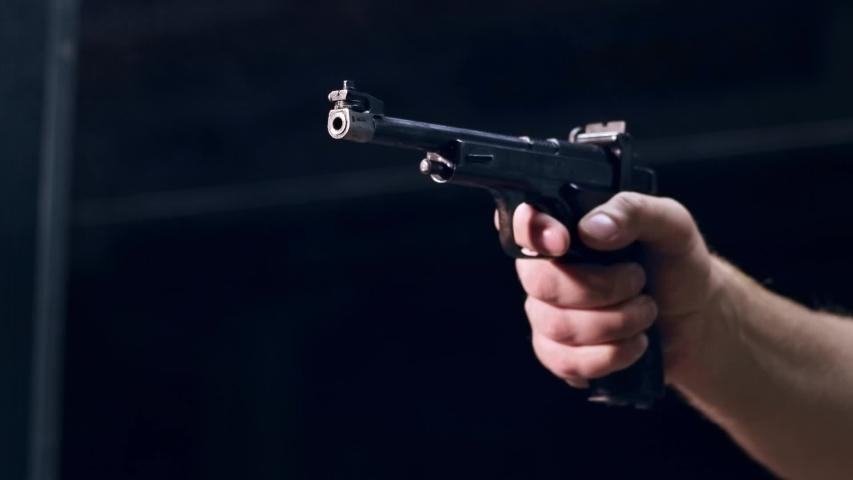 Shooting gallery. A young man preparing the gun and shooting with a firearms. A smoking gun. A concentrated young man shooting on a shooting range. Spark. Bullet. Shot.