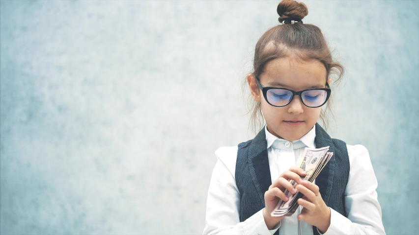 The small business lady stands on a gray background with dollars in her hands. During this, one denomination throws on the ground and shows the class. Smiles | Shutterstock HD Video #1038433127