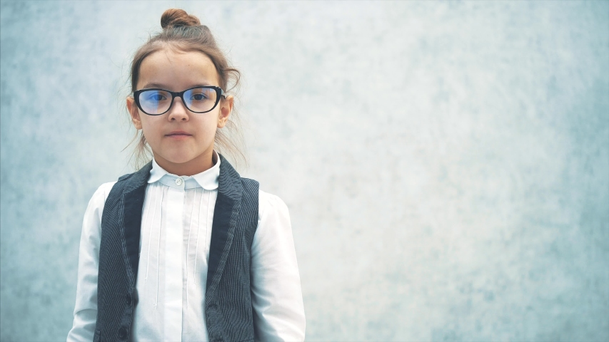 Close up the little lady boss stands on a gray background. During this time, hands raise glasses on the hair in the camera. Waving hands. | Shutterstock HD Video #1038433166