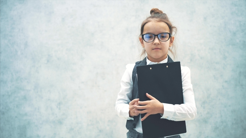 Clever little girl dressed in business clothes. During this time, holds a black folder. Lifting the leaf shows the inscription into the camera business. | Shutterstock HD Video #1038433700
