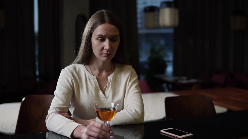 Having a drink. Beautiful young girl taking a sip of wine from a glass in the bar. Woman sitting at the bar with a glass of wine. 4K. | Shutterstock HD Video #1038483113
