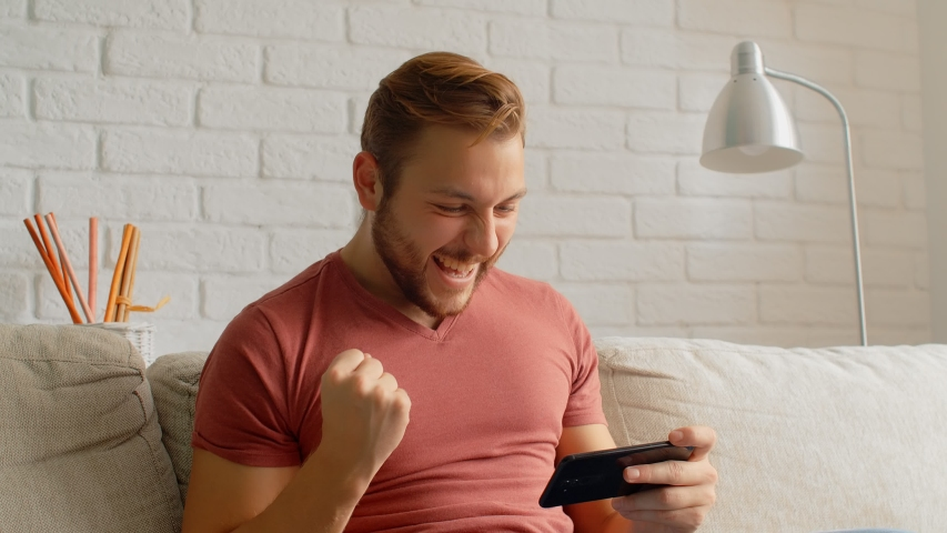 Sports Fan Reaction Concept - Excited sports fan watching his favourite team/player on smart phone, 4k | Shutterstock HD Video #1038485585