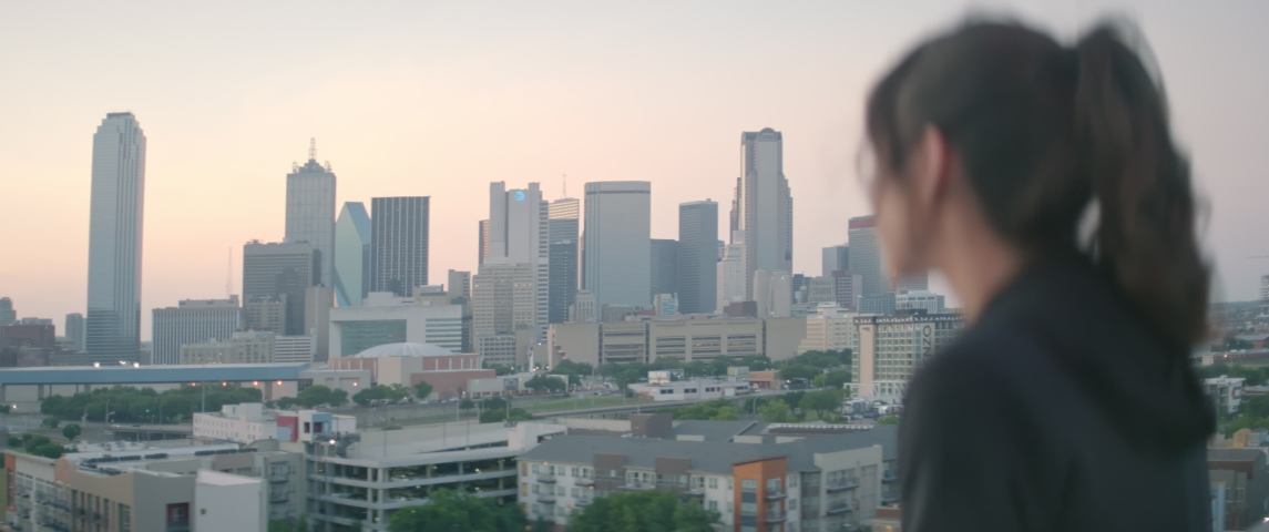 Woman overlooking Dallas Skyline at Sunset