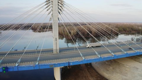 Truck moving on cable-braced bridge, camera fly around bridge over river and spring forest around