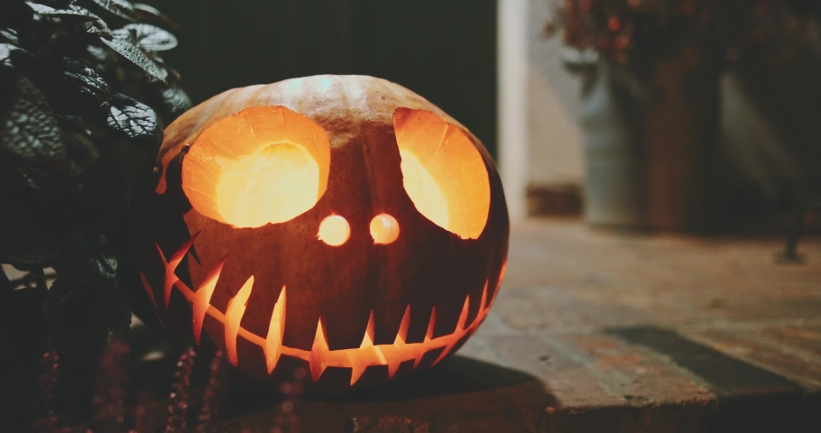 Halloween Carved Pumpkin on Front Porch. 4K. Jack-o'-Lantern decoration illuminating with burning candle inside. Autumn All Saints Day. | Shutterstock HD Video #1038490415