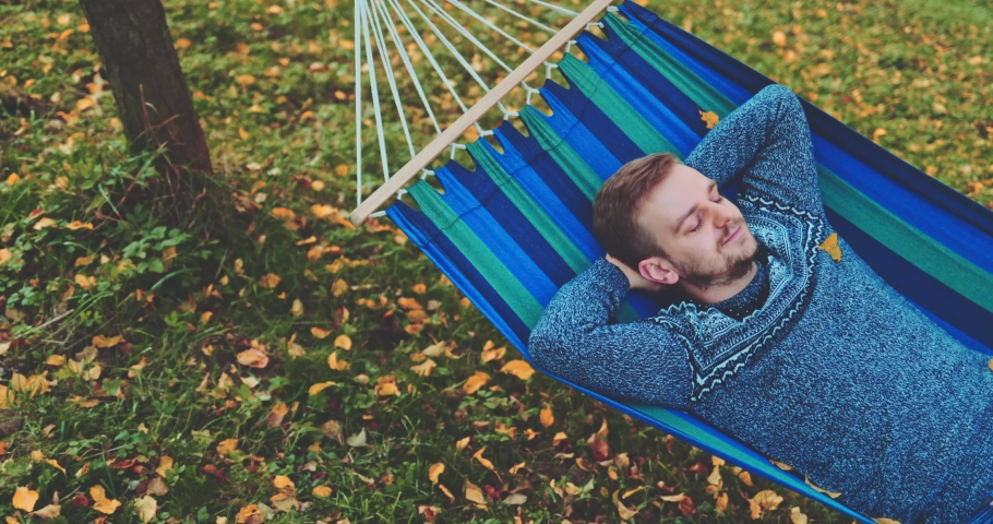 Man Relaxes in a Hammock in Autumn. SLOW MOTION. Handsome man daydreams, unwinds in a calm fall outdoor, rural country nature with colourful forest in background. Cozy season. | Shutterstock HD Video #1038490424