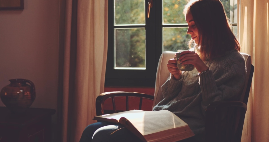 Woman Drinking Tea or Coffee and Reading a Book, Enjoying Cozy Morning. SLOW MOTION. Girl with a steaming cup of hot drink turning pages of a paper book. Cinematic Autumn aesthetics.
