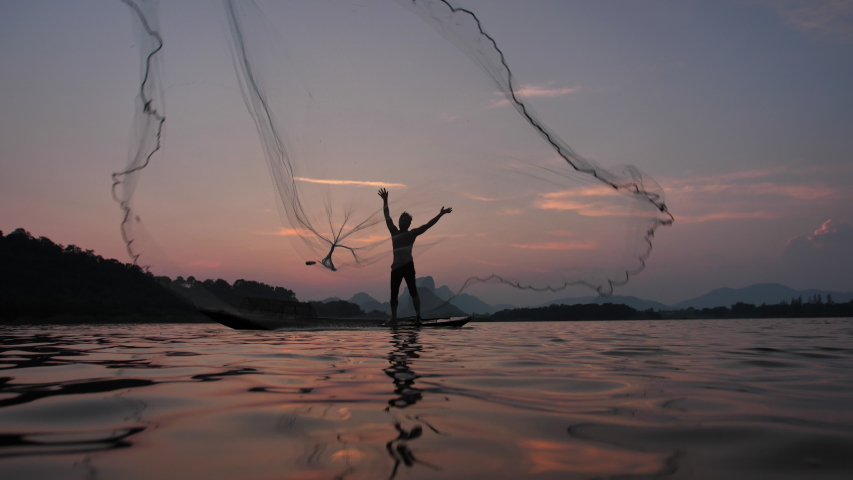 Slow Motion Silhouette of fishermen throwing fishing net during sunset with boats at the lake. Concept Fisherman's life style. Lopburi,  Asia, Thailand.  | Shutterstock HD Video #1038491372