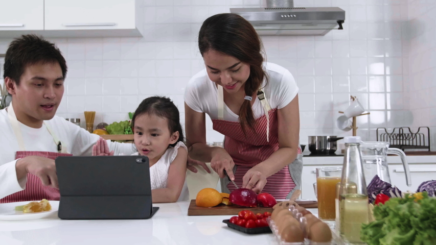 Happy Asian family make a cooking. Father, Mother and Daughter are preparing fruit apple and see Digital tablet in the kitchen at home. Healthy food concept and happy holidays | Shutterstock HD Video #1038491480