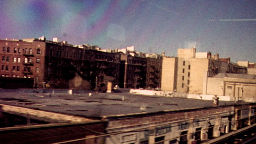 Retro looking archival footage filmed on New York City subway looking out through subway window at tracks and passing train with apartments and graffiti in the distance