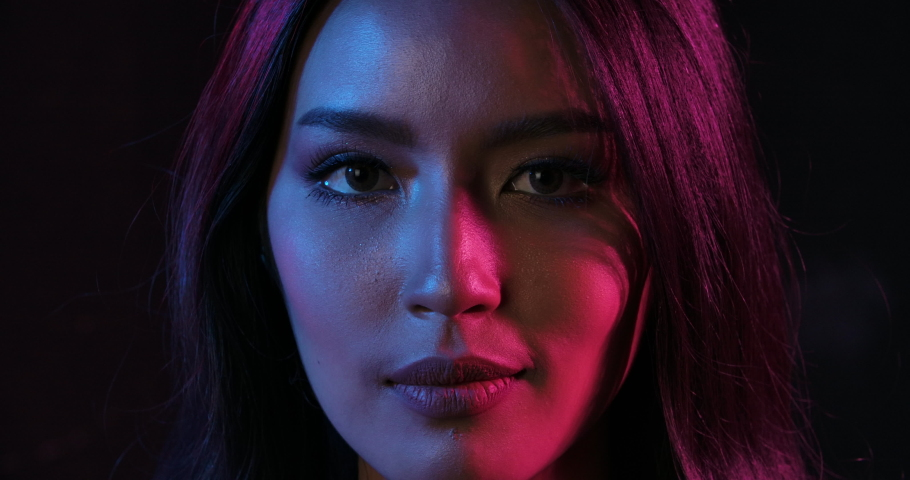 Close up Portrait shot of young flirting cute asian woman playfully posing for camera on the pink and blue neon lights in slow motion.  | Shutterstock HD Video #1038514028